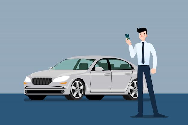 Homme d'affaires détenant la carte de crédit en face de la voiture.
