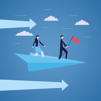 Homme d'affaires et femme avec drapeau sur avion en papier