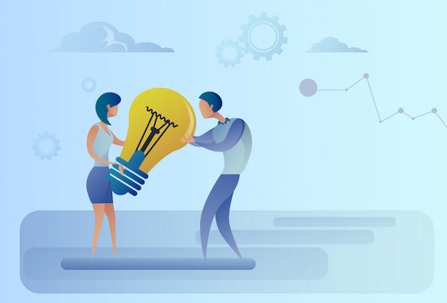 Homme d'affaires et femme tenant l'ampoule partage le nouveau concept d'idée créative