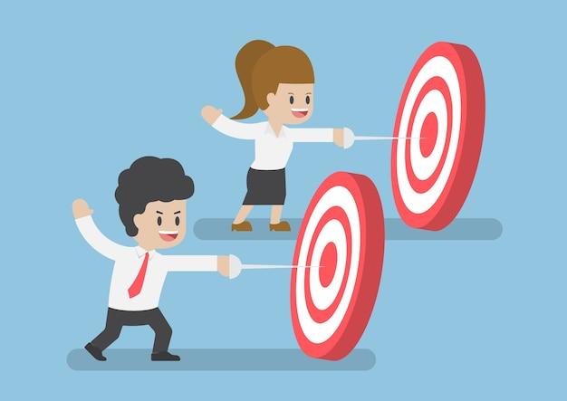 Homme d'affaires et femmes frappent le centre de la cible par l'épée, le concept de cible d'entreprise