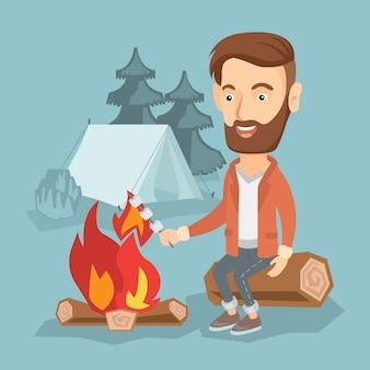 Homme d'affaires griller une guimauve sur un feu de camp.