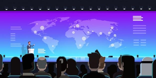 Homme d'affaires menant une présentation commerciale sur la carte du monde devant le groupe de gens d'affaires mee de formation