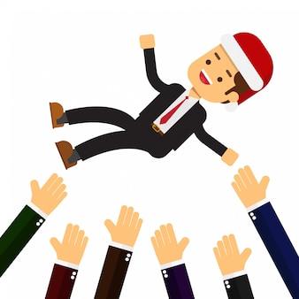Homme d'affaires de noël se jeter dans les airs par des collègues au cours de la célébration