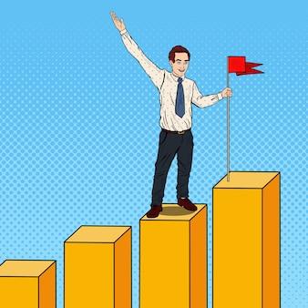 Homme d'affaires pop art avec drapeau en haut du graphique. la réussite des entreprises.