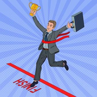Homme d'affaires pop art avec golden winner cup franchissant la ligne d'arrivée.
