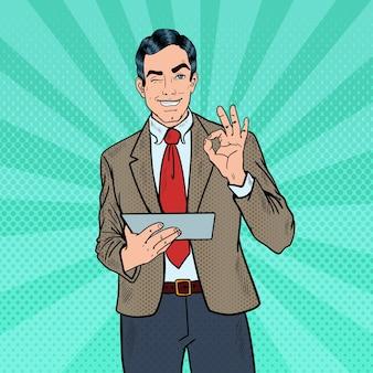 Homme d'affaires pop art avec tablette faisant des gestes ok et un clin de œil. illustration