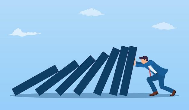 Homme d'affaires poussant contre la chute du pont de domino