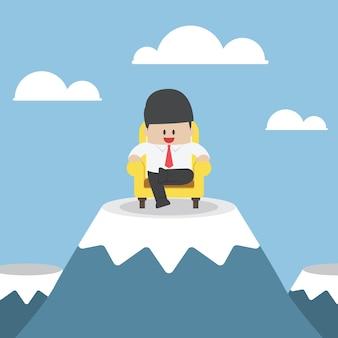 Homme d'affaires prospère est assis sur le canapé au sommet de la montagne