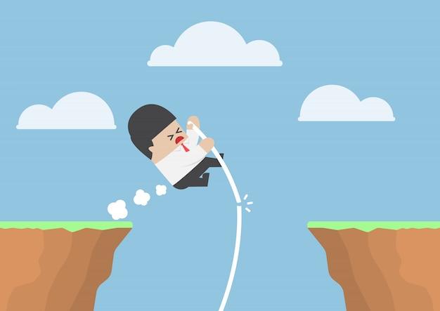Homme d'affaires saut à la perche à travers la falaise mais il échoue