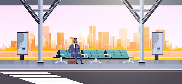 Homme affaires, séance, moderne, arrêt bus, homme affaires, à, valise, attente, transport public, sur, aéroport, station, paysage urbain, fond, horizontal, pleine longueur
