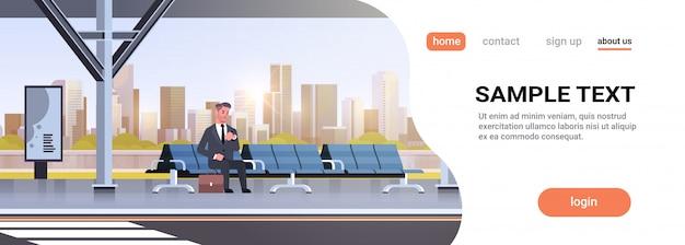 Homme affaires, séance, moderne, arrêt bus, homme affaires, à, valise, attente, transport public, sur, station aéroport, paysage urbain