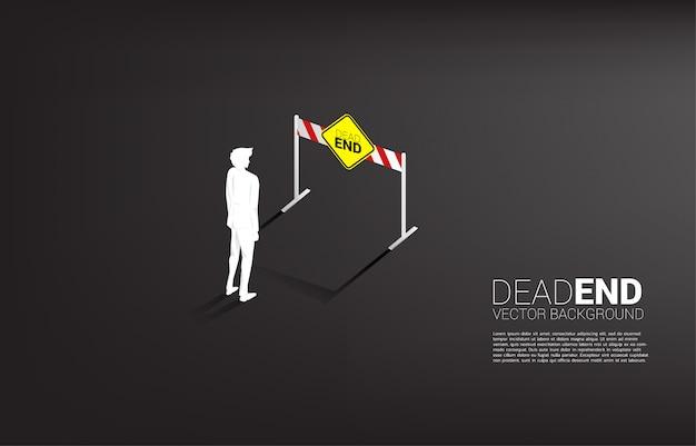 Homme d'affaires de silhouette debout avec signalisation impasse. mauvaise décision en entreprise ou en fin de carrière.
