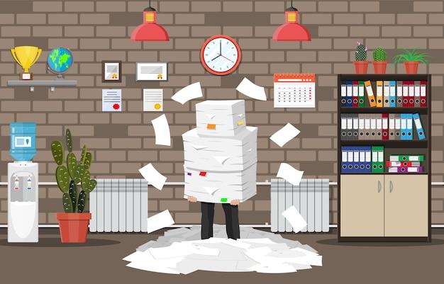 Homme d'affaires stressé sous une pile de papiers et documents de bureau.