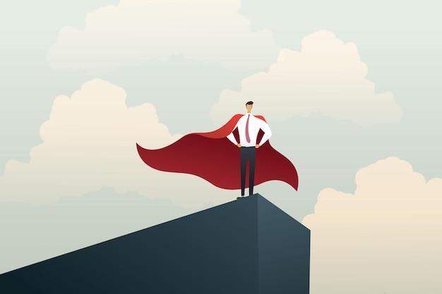 Un homme d'affaires de super-héros se tenant au sommet d'une falaise montre le succès de la puissance
