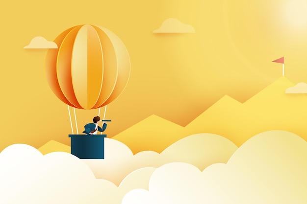 Homme d'affaires avec télescope en montgolfière à la recherche d'un drapeau rouge sur le sommet de la montagne.concept de réussite et d'affaires.illustration de papier art.