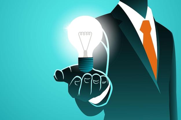 Homme d & # 39; affaires tenant une ampoule isolée sur bleu