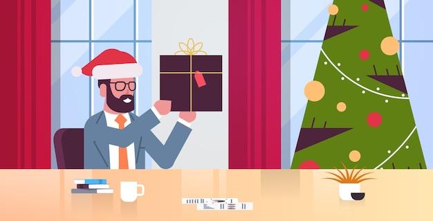 Homme d & # 39; affaires tenant cadeau boîte cadeau homme d & # 39; affaires assis au lieu de travail joyeux noël bonne année vacances d & # 39; hiver célébration concept bureau moderne illustration plat intérieur