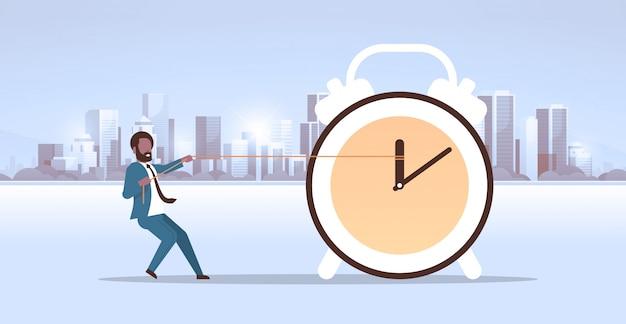 Homme affaires, traction, horloge, flèche, délai, temps, gestion, concept, homme affaires, repousser, heure, main, moderne, ville, bâtiments, paysage urbain, fond, horizontal, plat, pleine longueur