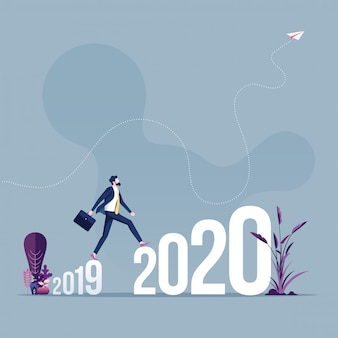 Homme d'affaires traversant entre 2019 et 2020 le nouvel an