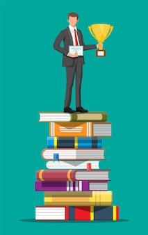 Homme d'affaires avec trophée sur pile de livres.