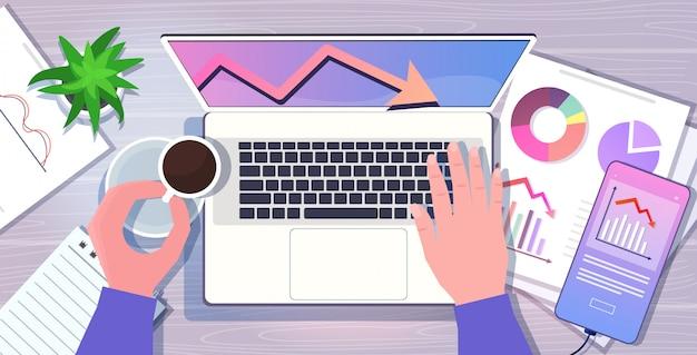 Homme d'affaires utilisant un ordinateur portable graphique à la baisse flèche économique tombant vers le bas de la crise financière