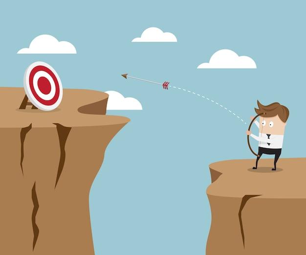 Homme d'affaires utilise l'arc et la flèche a frappé à la cible sur la falaise