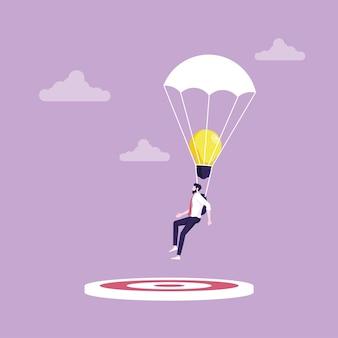 Un homme d'affaires utilise une idée pour cibler l'idée se résume à la cible avec une idée créative de parachute pour réussir