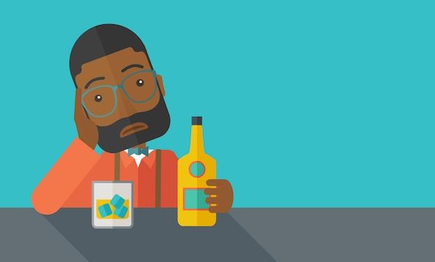 Homme africain triste seul dans le bar à boire de la bière.