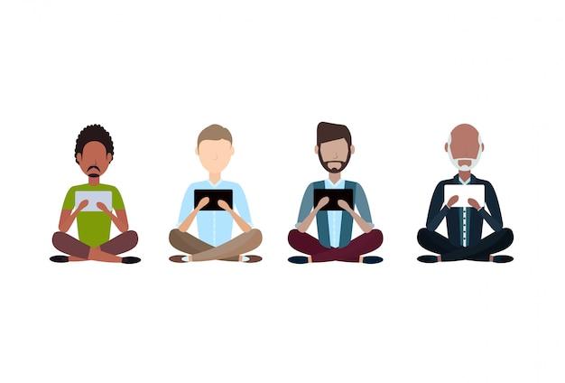 Homme d'âge différent assis pose à l'aide de tablette mix race personnage de dessin animé sans visage masculin