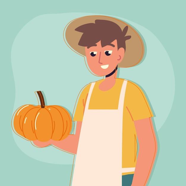 L'homme d'agriculteur tient la citrouille