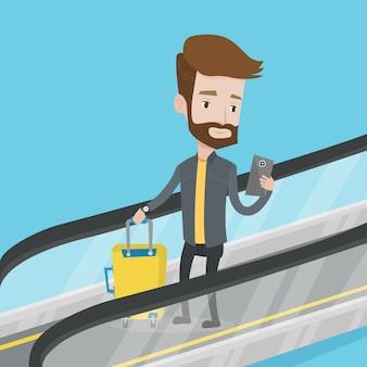 Homme à l'aide de smartphone sur l'escalator à l'aéroport.