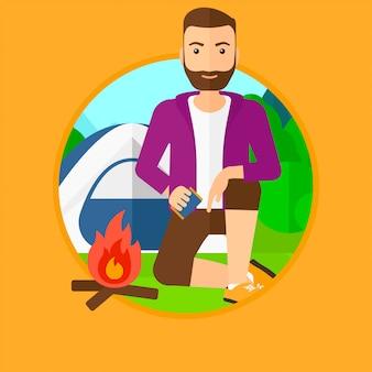Homme allumer un feu de camp.