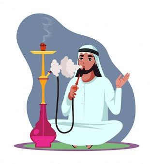 Un homme arabe fume une pipe à narguilé, expire une épaisse fumée blanche et assis sur le sol, se détend et passe du temps dans un bar à narguilé.