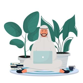 Homme arabe en vêtements traditionnels assis avec un ordinateur portable