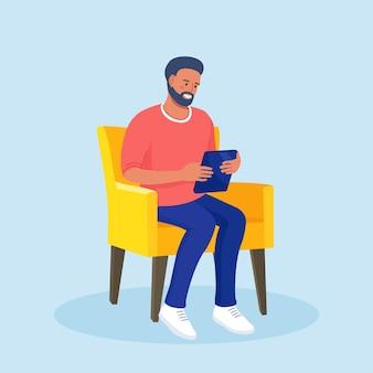 Homme assis sur une chaise et utilise un tablet pc. surfer sur internet ou lire un article. homme d'affaires discutant en ligne à la maison. des médias sociaux