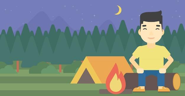 Homme assis sur un journal dans le camping.