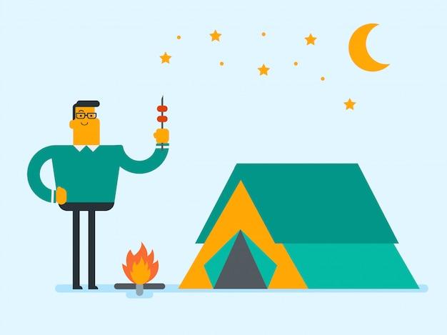 Homme assis sur un journal près du feu de camp dans le camping.