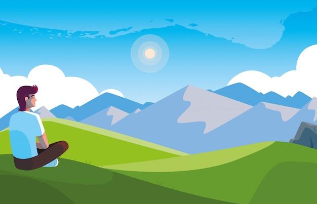 Homme assis en observant un paysage montagneux