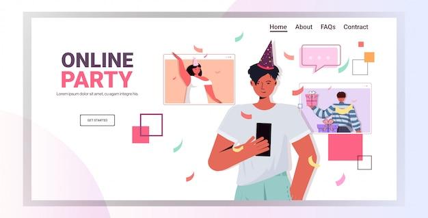 Homme au chapeau de fête à l'aide de smartphone célébrant la fête d'anniversaire en ligne