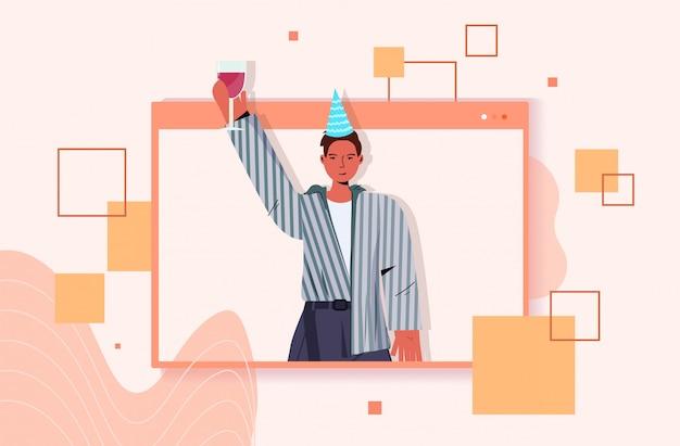 Homme au chapeau de fête célébrant la fête d'anniversaire en ligne