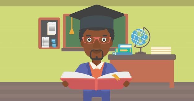 Homme au livre de tenue de graduation cap.