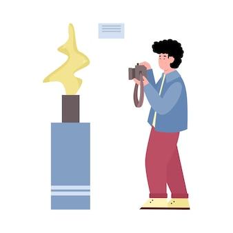 Un homme au musée prend une photo d'une illustration de dessin animé d'exposition
