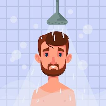 Un homme barbu se tient dans la salle de douche et de l'eau se déverse sur lui