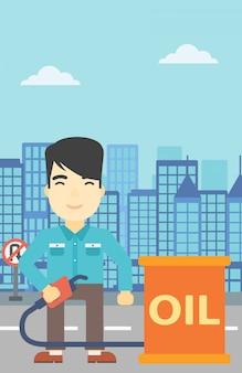 Homme avec baril de pétrole et buse de pompe à essence.