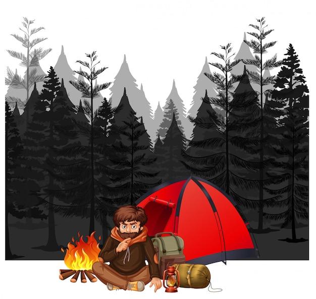 Un homme campant dans la forêt sombre