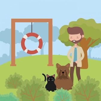Homme avec chien et chat dans le parc jouant des soins pour animaux de compagnie
