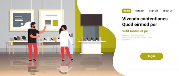 Homme consultant fournit expert client femme dans magasin de technologie moderne intérieur numérique ordinateur portable smartphone tv gadgets électroniques