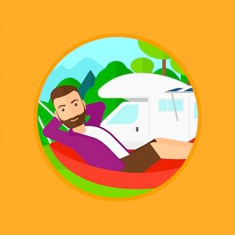 Homme couché dans un hamac devant le camping-car.