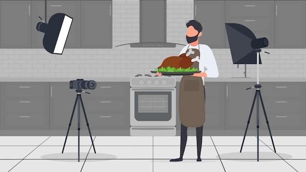 Un homme cuisinier dans la cuisine a un blog culinaire. le gars dans le tablier de cuisine tient du poulet frit. vecteur.