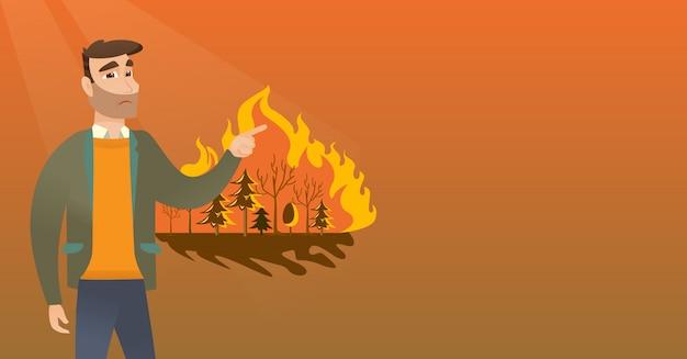 Homme debout à côté d'un feu de forêt.